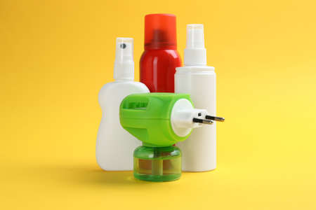 Set of different insect repellents on yellow background