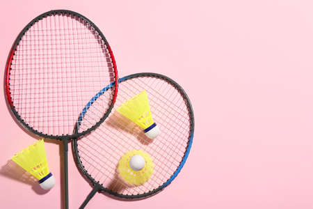 Badminton rackets and shuttlecocks on pink background, flat lay. Space for text
