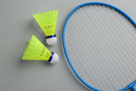 Badminton racket and shuttlecocks on grey background, flat lay