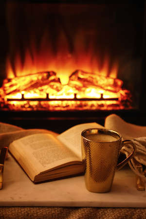 Cup of hot drink and book on blanket near fireplace indoors. Magic atmosphere