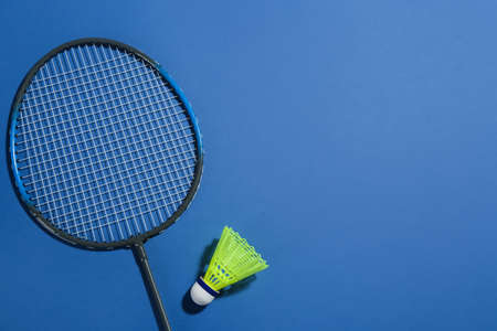 Badminton racket and shuttlecock on blue background, flat lay. Space for text
