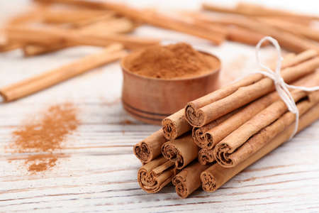 Aromatic cinnamon sticks on white wooden table, closeup. Space for text Reklamní fotografie