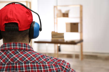 Worker wearing safety headphones indoors, back view. Hearing protection device