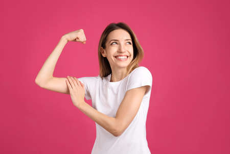 Strong woman as symbol of girl power on pink background. 8 March concept