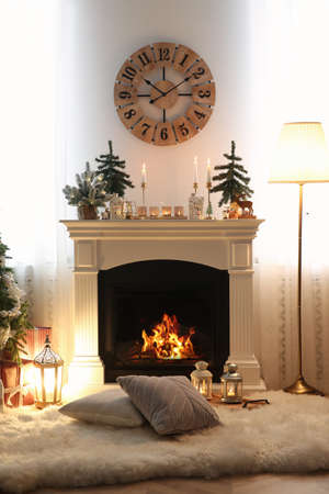 Small fir trees and candles on mantelpiece indoors. Christmas interior design