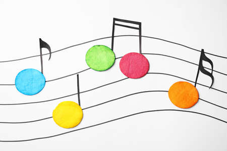 Dyed cotton pads as musical notes on white background, flat lay