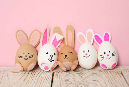 Eggs as cute bunnies on white wooden table against pink background. Easter celebration