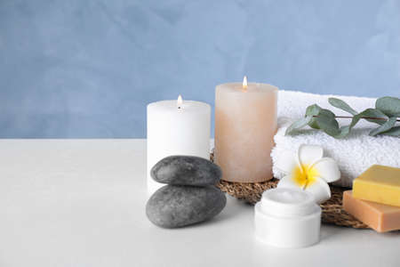 Composition with cream and burning candles on white table. Spa treatment Reklamní fotografie