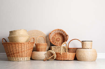 Many different wicker baskets made of natural material on floor near light wall
