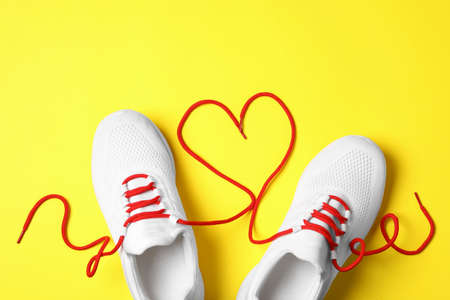 Stylish sneakers and red shoe laces in shape of heart on yellow background, flat lay Banco de Imagens