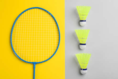 Badminton racket and shuttlecocks on color background, flat lay