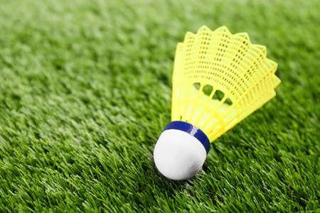 Badminton shuttlecock on green grass outdoors, closeup. Space for text