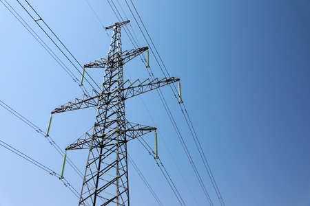 High voltage tower with electricity transmission power lines against blue sky, low angle view 版權商用圖片