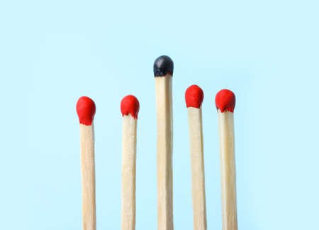 Row of whole matches and burnt one on light blue background. Uniqueness concept