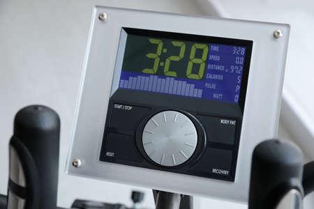 Control panel of modern elliptical machine cross trainer on blurred background