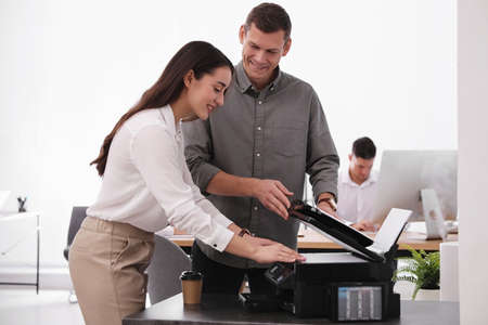 Employees using new modern printer in office Stock Photo