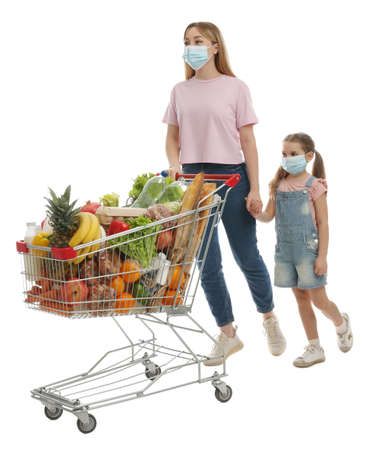 Mother and daughter in medical masks with shopping cart full of groceries on white background