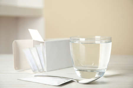 Medicine sachets, glass of water and spoon on white table