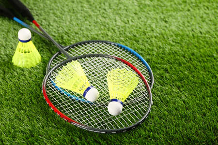 Badminton rackets and shuttlecocks on green grass outdoors, space for text