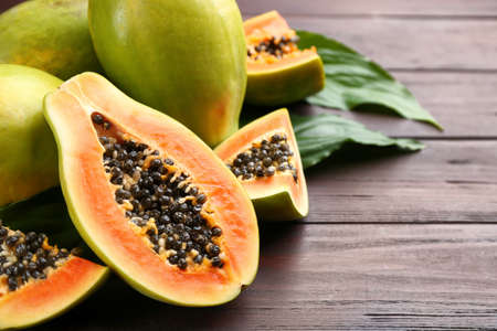 Fresh ripe papaya fruits with green leaves on wooden table. Space for text