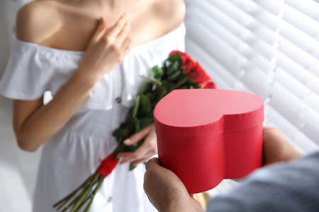Man presenting gift to his beloved woman at home, closeup. Valentine's day celebration Stock Photo