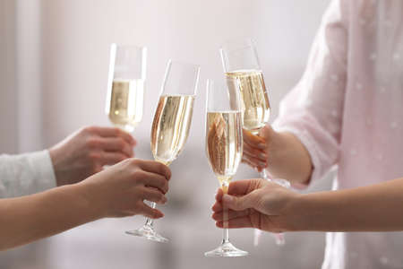 People clinking glasses of champagne against blurred background, closeup Stock Photo