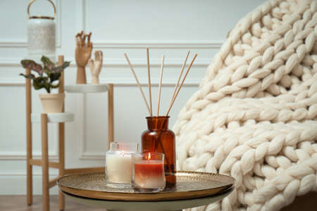 Air reed fresher and burning candles on table indoors. Interior elements