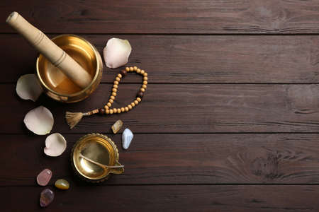Flat lay composition with golden singing bowl on wooden table, space for text. Sound healing
