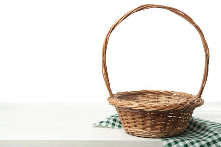 Empty wicker basket and cloth on wooden table against white background, space for text. Easter holiday