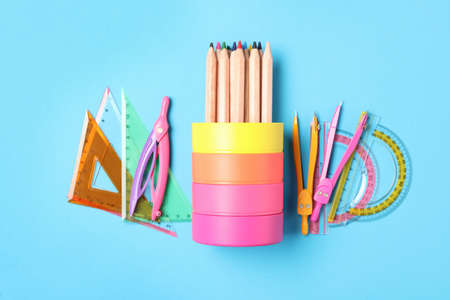 Different stationery on light blue background, flat lay. Back to school