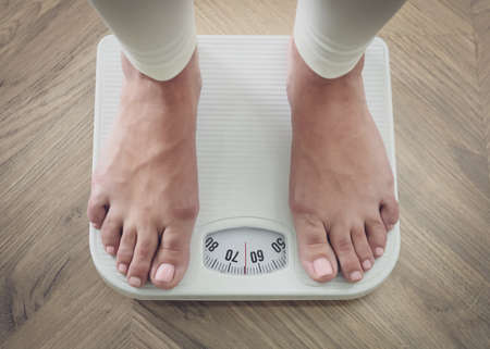Woman using scale on floor, closeup. Overweight problem after New Year party
