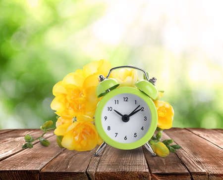Alarm clock and spring flowers on wooden table. Time change Stockfoto