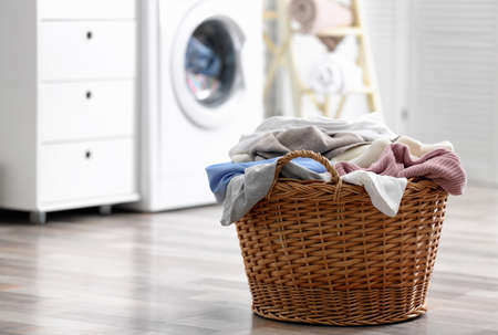 Wicker basket with dirty laundry on floor indoors, space for text