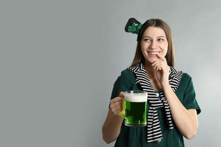 Happy woman in St Patrick's Day outfit with beer on light grey background, space for text