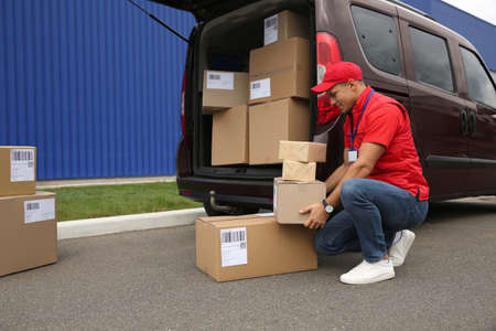 Courier loading packages in car trunk outdoors