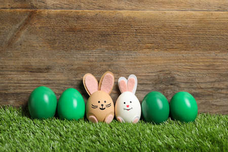 Two eggs as Easter bunnies among others on green grass against wooden background