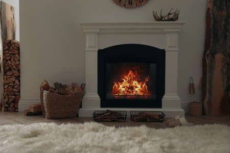 Firewood burning bright in elegant hearth indoors Standard-Bild