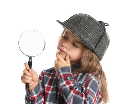 Cute little child in hat with magnifying glass playing detective on white background