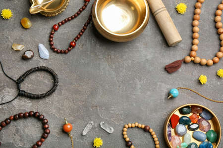 Frame of golden singing bowl and healing stones on grey table, flat lay with space for text
