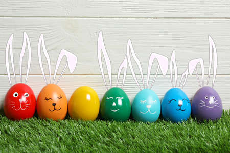 Colorful eggs as Easter bunnies on green grass against wooden background Stockfoto