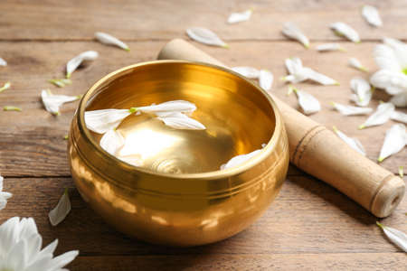 Golden singing bowl with petals and mallet on wooden table, closeup. Sound healing