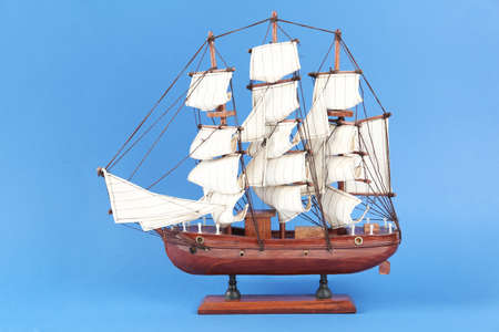 Miniature model of old ship with white sails on blue background