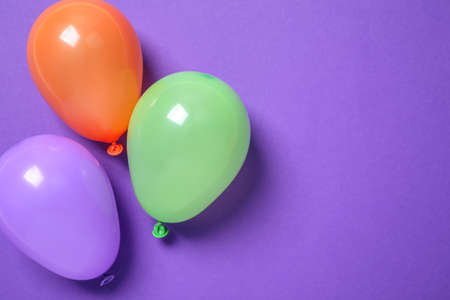 Colorful balloons on purple background, flat lay. Space for text
