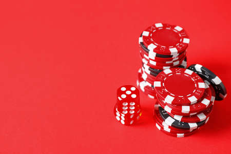 Poker chips and dices on red background, space for text