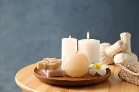Spa composition with candles and cosmetic products on wooden table, space for text Reklamní fotografie