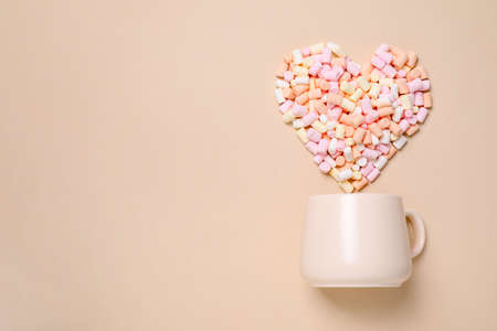 Cup and heart made of marshmallow on beige background, flat lay. Space for text