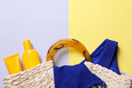 Beach bag with sun protection cosmetic products and swimsuit on color background, flat lay. Space for text Reklamní fotografie