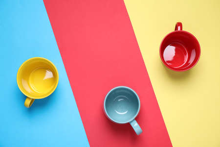 Different bright ceramic cups on color background, flat lay Reklamní fotografie