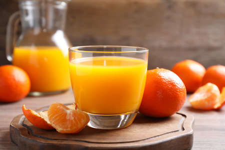 Glass of fresh tangerine juice and fruits on wooden board