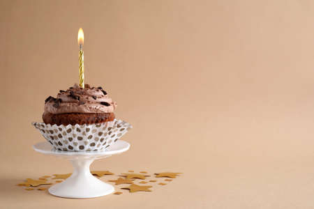 Chocolate cupcake with burning candle on beige background. Space for text